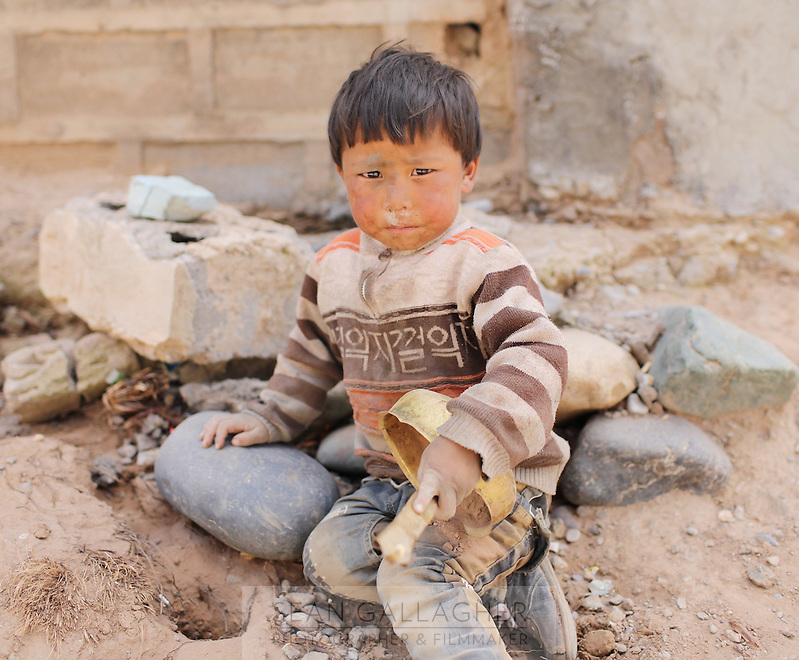 A young Tibetan boy in a relocation village in the Amdo region of the Tibetan Plateau. Up to 100,000 nomads have been removed from the highland grasslands of the Tibetan Plateau. Climate change, mining and government policy are causing the rapid disappearance of this unique culture.