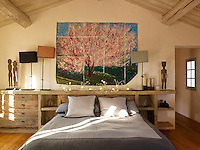 A large drawing of a cherry tree hanging behind the bed in the bedroom of interior designer Marjolaine Leray's chateau in the South of France