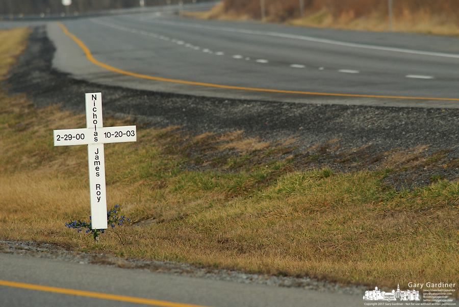 A roadside memorial of a cross and small arrangement of plastic flowers marks the site of a fatal vehicle accident along a divided highway in rural West Virginia.<br />
