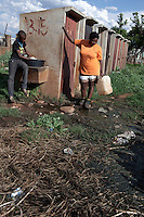 KHUTSONG, SOUTH AFRICA - OCTOBER 16: Residents fetch water at a tap next to communal toilets on October 16, 2012, in Khutsong, South Africa. Khutsong, a black township. is located about 56 miles west of Johannesburg, and surrounded by gold mines. Because of recent strikes many mineworkers has been fired which is making the poverty worse here. The communal toilets are dirty and often broken. (Photo by Per-Anders Pettersson)