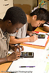 Education High School Mathematics class two male students working individually at table using calculators vertical
