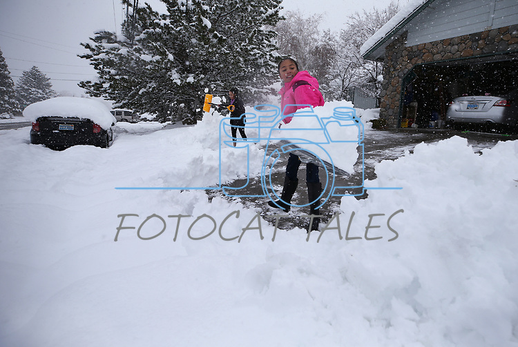 Jailey Tijerina, 10 and her mom Trinana shovel more than a foot of snow in Carson City, Nev., on Friday, March 16, 2018. <br />