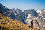 a hiker at sundance pass in the absaroka beartooth wilderness in montana. mountain peaks above 12000 feet all around.