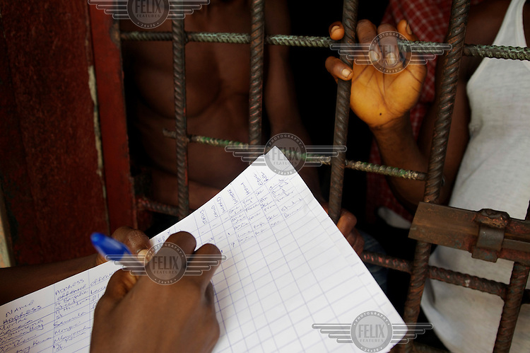 Baindu Koroma, a paralegal who works for Timap for Justice, speaking to men detained in the cells and taking case notes at Bo central police station.   <br /> Her work includes making regular visits to police stations, the prison, and the courts to monitor whether people are being afforded their lawful rights, for example, the right to bail, legal representation, detention without charge, etc, and if not to advocate on their behalf.
