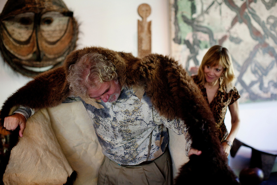 Los Angeles, California, November 14, 2009 -  Ernie Wolfe wraps himself in a buffalo  skin while his wife Diane helps him. Ernie shot the buffalo earlier this year and has the head mounted in his bedroom. The Wolfe's own the Ernie Wolfe Gallery and are the most reknowned African at dealers in the country. ..CREDIT: Daryl Peveto/LUCEO for The Wall Street Journal.Homefront - Ernie Wolfe #1348.