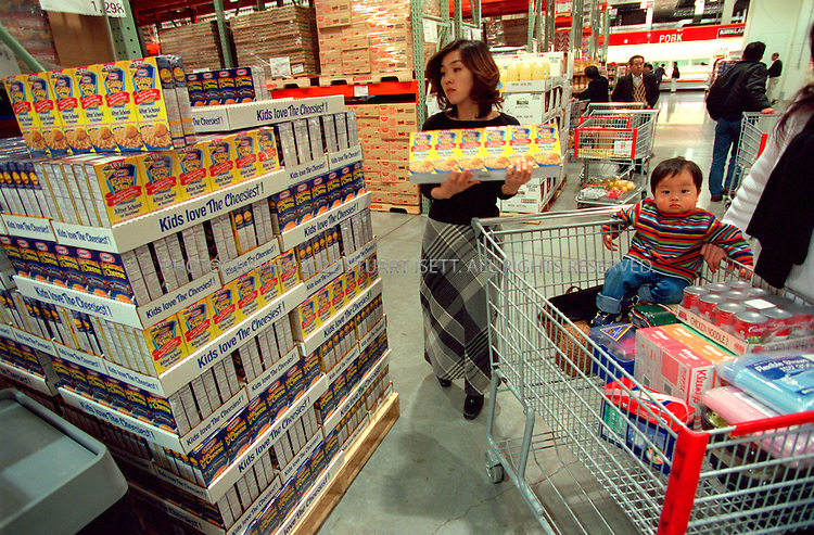 2/26/01--Chiba, Japan..A Japanese mother loads up on a jumbo serving of Kraft Macaroni and Cheese at Costco, the American grocery chain attempting to penetrate the Japanese market....All photographs ©2003 Stuart Isett.All rights reserved.This image may not be reproduced without expressed written permission from Stuart Isett.
