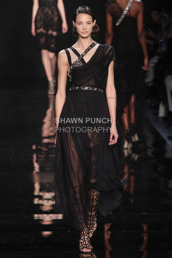 """Model walks runway in an asymmetric black silk chiffon dress with embroidered detail from the Reem Acra Fall 2016 """"The Secret World of The Femme Fatale"""" collection, at NYFW: The Shows Fall 2016, during New York Fashion Week Fall 2016."""
