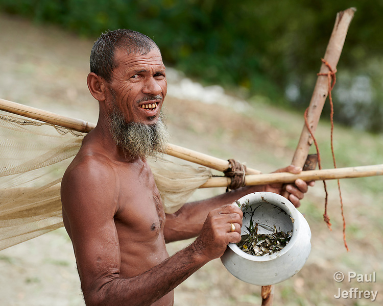 A man shows the fish he caught with a net in Kunderpara, a village on an island in the Brahmaputra River in northern Bangladesh.