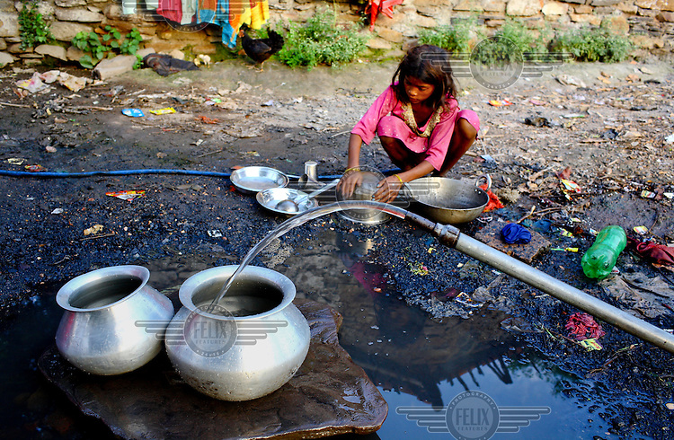 A young girl fills water vessels from a pipe that supplies her village. /Felix Features
