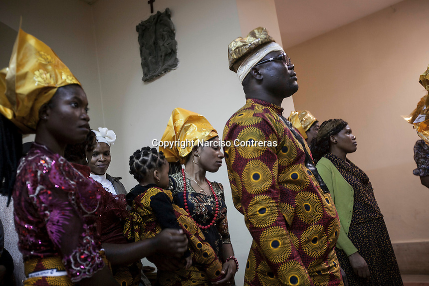 November 14, 2014 - Tripoli City, Libya: Sub-Saharan migrants wear Nigerian traditional clothes as they celebrate at the Christian church in Tripoli City. Often chased and jailed by smugglers and authorities migrants hide themselves among the church's community. Libya's revenues from smuggling trade including human trafficking is up to 10% of the national GDP, making this one of the most profitable illegal business across the country. In spite of the international concern of human rights violations, Sub-Saharan migrants risk their lives across Libya, often jailed, sold and kidnapped during their hazardous trip through the Sahara desert to the coastal ports as most of them attempt to reach Europe. (Photo/Narciso Contreras)