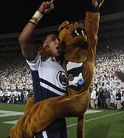 State College, PA - 10/12/2013:  The Nittany Lion and a cheerleader celebrate a PSU score during the game.  Penn State defeated Michigan by a score of 43-40 in 4 overtimes on Saturday, October 12, 2013, at Beaver Stadium.<br /> <br /> Photos by Joe Rokita / JoeRokita.com