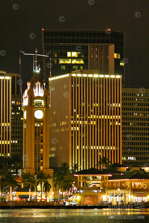 Night photo of Aloha tower and Aloha tower marketplace along Honolulu harbor. Downtown Honolulu in background. Oahu.