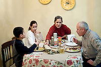 John Woodard (cq), his wife, Martha Woodard (cq), and their children Ashley Woodard (cq, age 11), and John Woodard Jr. (cq, age 9) eat dinner at home in Laredo, Texas, US, Thursday, Dec. 10, 2009. Because of the slumping economy, John is looking into getting another job to make ends meet. Martha, a native Spanish speaker from Mexico, is learning English, in part, to help take over managing their apartment business and be able to answerphone calls in English. Martha also wants to learn English to be able to help her children with homework, which is always in English...PHOTOS/ MATT NAGER