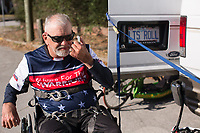 Morehead City, NC -- Quadriplegic hand cyclist Paul Kelly, 62, adjust a mirror attached to his sunglasses before a training ride for the Boston Marathon Tuesday, March 27, 2018. (Justin Cook for The Wall Street Journal)<br /> <br /> SUMMARY:<br /> <br /> Paul Kelly, hand cyclist, Beaufort, NC Training for the Boston Marathon so we would want to shoot in March to run the week before the marathon or marathon Monday, Apriln16. Life as a quadriplegic doesn't keep 62-year-old Paul Kelly on the sidelines. After breaking his neck in a swimming accident in 1978, Kelly was determined to find fitness activities to maintain an active lifestyle. He discovered handcycles while watching his niece compete in the 2006 Marine Corps Marathon and was inspired to start his own marathon career to stay fit. Paul has competed in over 100 half and full marathons. On April 16, he will celebrate his 40th year of living as a quadriplegic by taking on one of the most coveted races for a marathoner -- the Boston Marathon. Kelly is among the 60 handcyclists competing in the 2018 Boston Marathon with a qualifying time of 1:26:37. Most of Paul's distance training takes place at Bogue Banks, which includes Atlantic Beach, Salter Path, and Emerald Isle, N.C. It's Nicholas Sparks worthy scenery with its marshes, waterways, inlets and small islands. Paul is particularly fond of the approach from Atlantic Beach to Bogue Banks -- it's via the high-rise bridge. In cold weather, Paul has to be mindful of the environment and dress in a manner that insulates his legs while also allowing his upper body to ventilate. Paul chooses to train at times of day when the temperatures are more reasonable. He uses hand warmers in his gloves, on the inside the grips on his handcycle and in the legs of his trousers.