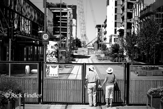 A couple peer through the perspex into The Red Zone in Christchurch.
