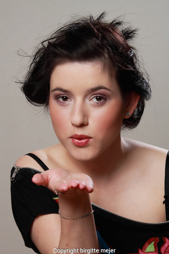 Model blowing Kisses towards the camera. Model wearing the dark hair up, and wearing a black blouse with a zipper.