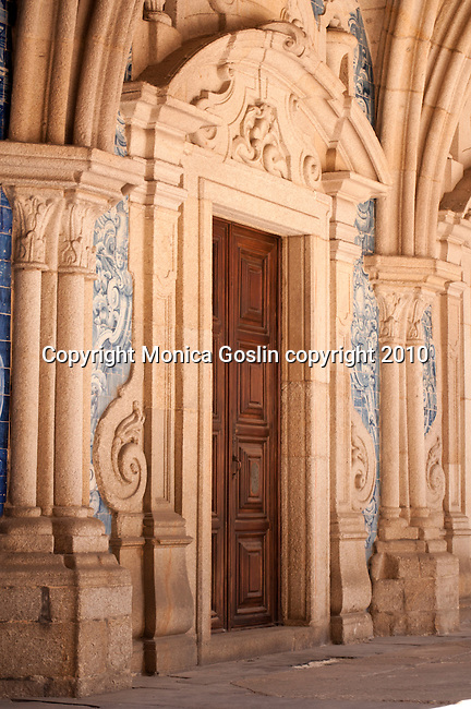 A door surrounded by carved stone and azulejos (blue and white tiles) in the Gothic cloister of the Cathedral of Porto, Portugal.