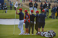 Bryson Dechambeau (Team USA) holds the pin on 18 as Alex Noran (Team Europe) drains a long birdie putt during Sunday's singles of the 2018 Ryder Cup, Le Golf National, Guyancourt, France. 9/30/2018.<br /> Picture: Golffile | Ken Murray<br /> <br /> <br /> All photo usage must carry mandatory copyright credit (&copy; Golffile | Ken Murray)