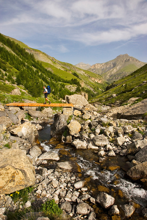 Hiker crosses a bridge over a mountain stream on the GR5 long distance foothpath in the Vallon de Sallevieille on the ascent to Mont Mounier with Las Donnas in the background.  Parc National du Mercantour. Alpes-Maritimes. Provence, France.