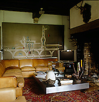 A painting by Roger Nellens hangs on the wall behind  the leather L-shaped sofa in his cosy living room