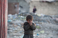 The Chamne Babrak refugee camp in Kabul 5-1-14 A child shivers in the cold.