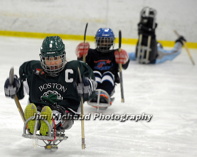 (Everett MA 01/31/15) Catherine Faherty, 10, of Norwell, gives it her all, as Delmace Mayo, 8, of Jamaica Plains, is right behind her, while Gavin Ford, 10,  of North Reading, has a little bit of difficulty,  as they participate in a drill during sled hockey class for the disabled, Saturday, January 31, 2015, at the Allied Veterans Memorial Rink in Everett. Herald Photo by Jim Michaud