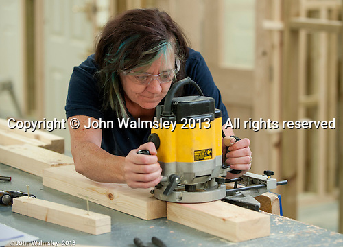 Woman using a router while making a sash window frame.  Carpentry and joinery training, Able Skills, Dartford, Kent.