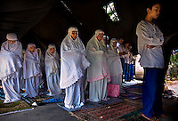 Kartini Emergency School students pray alongside the 'Twin Teachers' (front middle) underneath the tent where their temporary school is currently located at in North Jakarta. Since the early 1990s, twin sisters Sri Rosyati (known as Rossy) and Sri Irianingsih (known as Rian) have used their family inheritance to set up and run 64 schools in different parts of Indonesia, providing primary education combined with practical skills to some of the country's most deprived children.