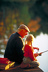grandfather fishing with granddaughter