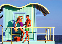 Young couple at lifeguard stand on beach