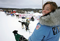 Volunteer checker Stacy Merrill from Anchorage holds Gerald Sousas lead dogs at Ruby on Saturday morning while he checks in
