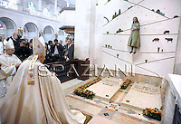 Pope Benedict XVI prays before the three little shepherds' tomb during the traditional annual celebrations at Fatima's Sanctuary in Portugal on May 13, 2010. The mass marks the anniversary of the day in 1917 when three shepherd children reported to have seen the first of a series of apparitions of the Virgin Mary, turning the Portuguese village into one of the biggest draws for the Roman Catholic faithful