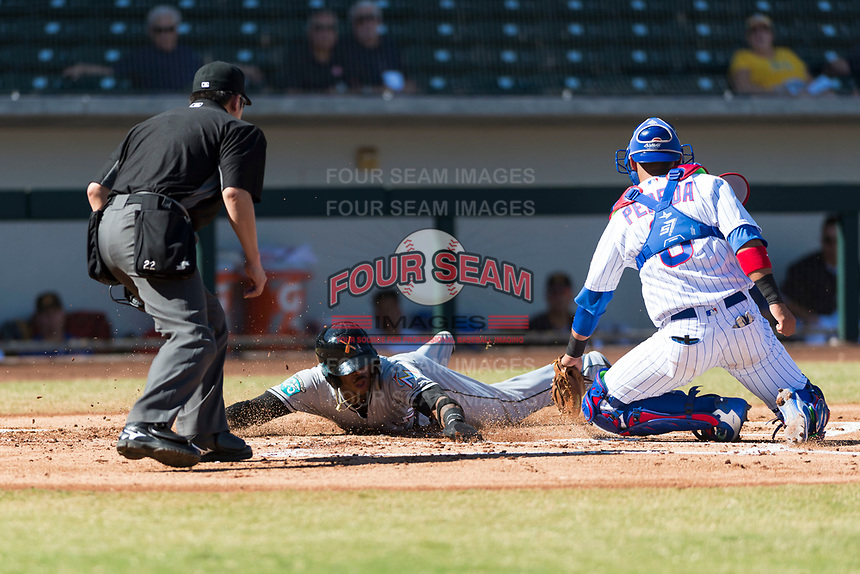 Salt River Rafters right fielder Monte Harrison (4), of the Miami Marlins organization, slides safely across home plate in front of catcher Jhonny Pereda (6) and home plate umpire Chikara Tsugawa during an Arizona Fall League game against the Mesa Solar Sox at Sloan Park on October 30, 2018 in Mesa, Arizona. Salt River defeated Mesa 14-4 . (Zachary Lucy/Four Seam Images)