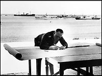 BNPS.co.uk (01202 558833)Pic:    Pen&Sword/BNPS<br /> <br /> Gereral Rommel is pictured plotting his first attacks against his enemy, 1941.  Behind him are transport ships in the bay outside Tripoli.<br /> <br /> Fascinating rare photos of Rommel's feared Afrika Korps which terrorised the Allies in the desert have come to light in a new book.<br /> <br /> Under the direction of legendary German commander Field Marshal Erwin Rommel, who was nicknamed the Desert Fox, the corps were recognised as a superb fighting machine.<br /> <br /> They achieved their greatest triumph when they outmanoeuvred the British at the Battle of Gazala in June 1942 which led to them capturing Tobruk in Libya.<br /> <br /> But they were ultimately defeated in the iconic Battle of Alamein when they succumbed to an offensive led by Field Marshal Bernard Montgomery.