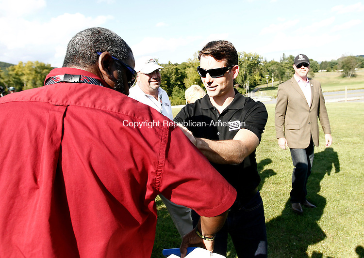 """Lime Rock, CT- 18 September 2014-091814CM03- NASCAR star Jeff Gordon, right, signs an autograph for Greg Holt of Danbury during Jeff Gordon's """"Drive to End Hunger"""" fundraiser at Lime Rock Park on Thursday.    Christopher Massa Republican-American"""