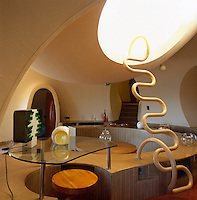 A futuristic ladder leads to a mezzanine seating area above this circular dining space with a built-in banquette
