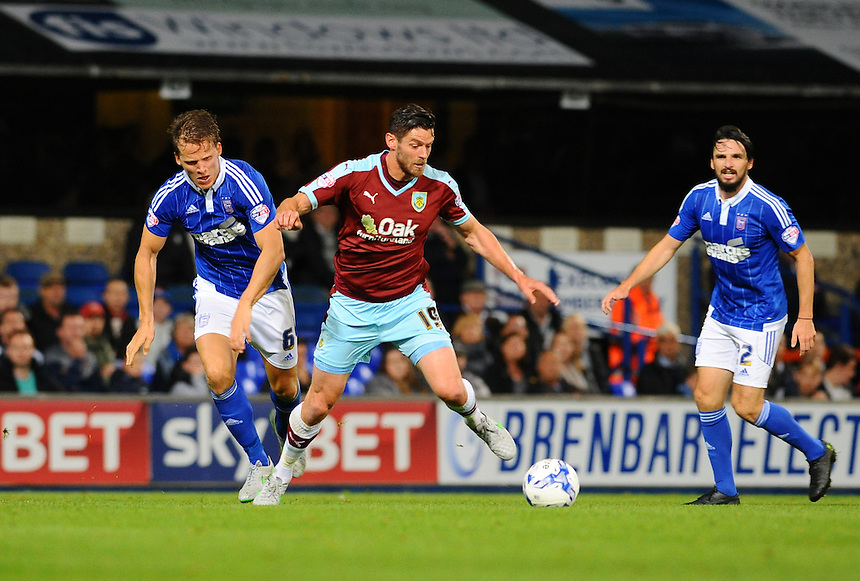 Burnley's Lukas Jutkiewicz (c) gets to the ball before Ipswich Town's Christophe Berra<br /> <br /> Photographer Ashley Pickering/CameraSport<br /> <br /> Football - The Football League Sky Bet Championship - Ipswich Town v Burnley - Tuesday 18th August 2015 - Portman Road - Ipswich<br /> <br /> &copy; CameraSport - 43 Linden Ave. Countesthorpe. Leicester. England. LE8 5PG - Tel: +44 (0) 116 277 4147 - admin@camerasport.com - www.camerasport.com
