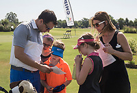 NWA Democrat-Gazette/CHARLIE KAIJO Cooper Allen of Rofers, 6, (in orange) looks at his score sheet with his family (from left) Chris Allen and mom Katie Allen with sisters Paige, 10 and Avery, 9 during a junior golf tournament, Sunday, June 10, 2018 at The First Tee Learning Center in Lowell.<br />