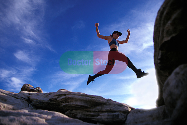 healthy young athletic woman leaping across rock crevasse while hiking