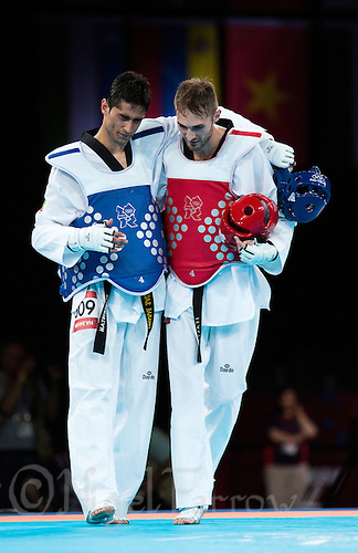 10 AUG 2012 - LONDON, GBR - Mauro Sarmiento (ITA) (right) of Italy helps Nesar Bahawi (AFG) (left) of Afghanistan back to his coach after winning the men's -80kg category bronze medal B contest at the London 2012 Olympic Games Taekwondo at Excel in London, Great Britain (PHOTO (C) 2012 NIGEL FARROW)