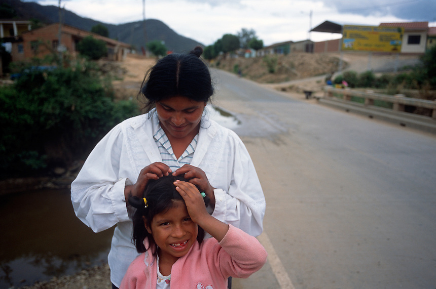 "A mother arranges her daughter's hair along the road in Los Negros, Bolivia Friday, Nov. 12, 2004. Ernesto ""Che"" Guevara was captured by the Bolivian army in 1967 in a nearby valley and executed in La Higuera days later. His body was put on public display in the laundry room of the Vallegrande hospital, then secretly buried under the air strip for 30 years. Guevara and fellow communist guerillas were attempting to launch a continent-wide revolution modeled on Guevara's success in Cuba in the late 1950s. The Bolivian government recently began promoting the area where he fought, was captured, killed and burried for 30 years as the ""Ruta del Che,"" or Che's Route. (Kevin Moloney for the New York Times)"