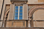 Architectural detail of a fresco of a lion, and antique arches and columns around a window of a building in Bergamo, Italy
