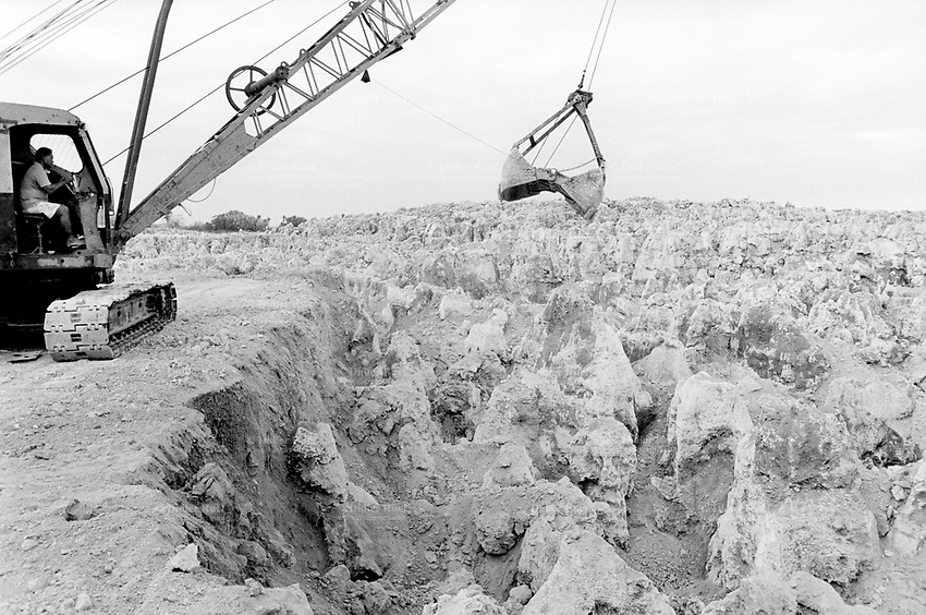 """Republic of Nauru. Central Pacific. Nauru is a tiny island (21 square-km). Nauru Phosphate Corporation. A crane at work on Top Side. Mined out coral pinnacles from large deposits easily accessible high-grade phosphates. For millions of years billions of birds nested on Nauru and the excrement or guano ( phosphoric acid and nitrogen) they left behind reacted through leaching with the coral (lime) of the upraised atoll to form a hard, colorless rock averaging 85-88 % pure phosphate of lime. The primary deposits of phosphate are almost mined out, leaving four fifth of the island ressembling a ghostly landscape. The mining has produced dramatic consequences through the destruction of the vegetation and climatic changes. Over-mining has led to an """"oven"""" effect: a bald plateau so hot the updraft disperses clouds and leads to drought. © 1999 Didier Ruef"""