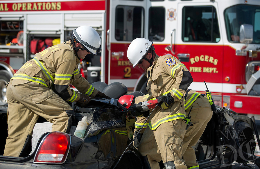 NWA Democrat-Gazette/JASON IVESTER<br /> Rogers Fire Cpt. Joey Everhart (left) and firefighter James Copeland cut through a vehicle on Thursday, Sept. 8, 2016, at U Pull It Auto Parts in Rogers. Rogers Fire Department special operations personnel were working in three-man rotations competing against the clock to strip the car down into pieces small enough to pass through a 22.5&quot; tire. The competition allows them to better learn their tools as well as vehicular construction to assist them in extrications.