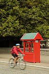 Cyclist riding past red phone booth in downtown Christchurch, New Zealand