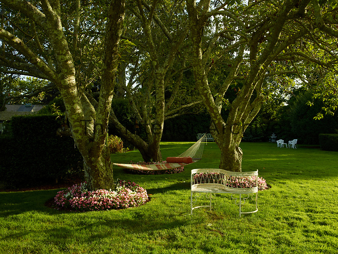 Flower beds of pretty pink and white flowers encircle the bases of trees. A hammock is strung between the trees and provides the perfect shady spot for relaxing in the garden. A wrought-iron loveseat is set amongst the trees.