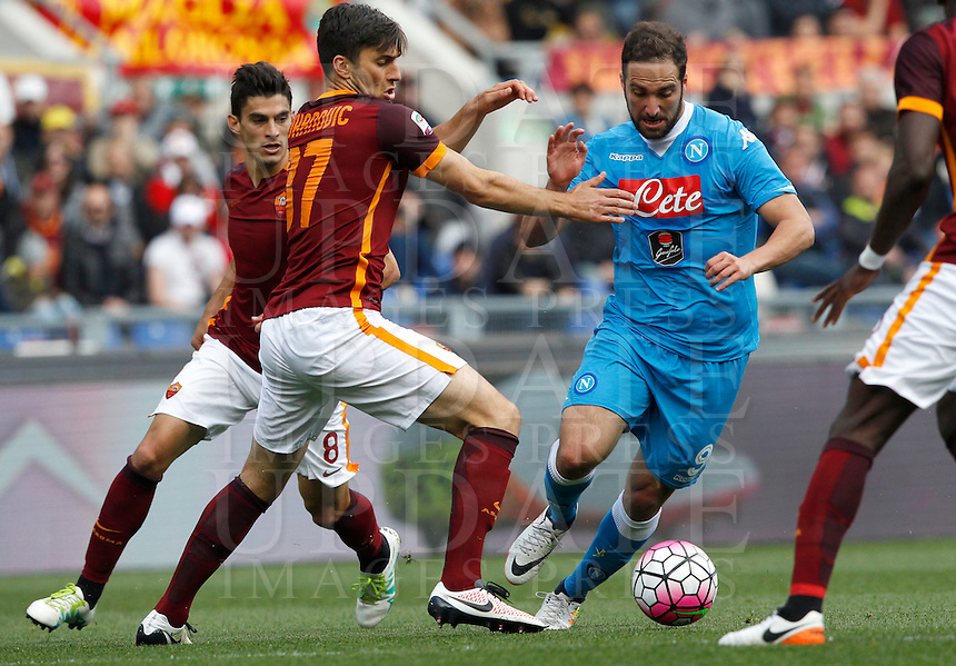 Calcio, Serie A: Roma vs Napoli. Roma, stadio Olimpico, 25 aprile 2016.<br /> Napoli's Gonzalo Higuain, right, is challenged by Roma's Ervin Zukanovic, center, and Diego Perotti during the Italian Serie A football match between Roma and Napoli at Rome's Olympic stadium, 25 April 2016.<br /> UPDATE IMAGES PRESS/Riccardo De Luca