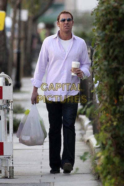 Shane Warne spotted near Liz Hurley's home, London, England..October 14th, 2011.full length black trousers purple shirt carrier bag plastic shopping takeaway cup drink beverage sunglasses shades.CAP/HIL.©John Hillcoat/Capital Pictures .