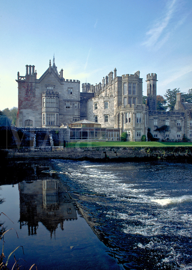 The impressive image of Adare Manor or castle is mirrored on a quiet, blue reflecting pond. This is one of the great manor house hotels of Ireland. Adare, Ireland.