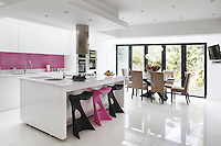This sleek white kitchen with its hints of candy pink proves that minimal design need not be clinical